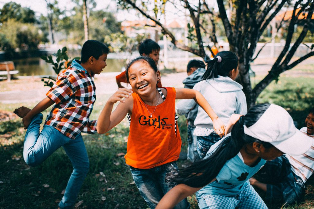 Image of children playing in the park, with a girl smiling and wearing an orange vest which has the world girls written on it.